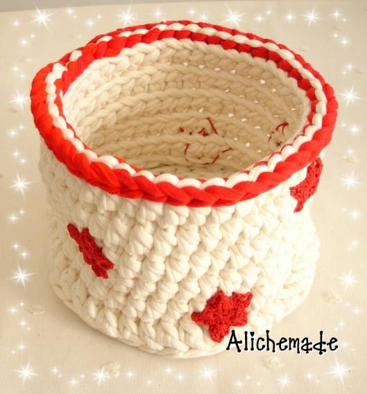 Cesto redondo de trapillo blanco y borde rojo, con estrellas de ganchillo rojas.